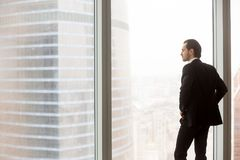 Serious young businessman standing in modern office, looking out royalty free stock photos