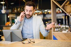 Serious young businessman talking on a phone, working in a cafe stock photography