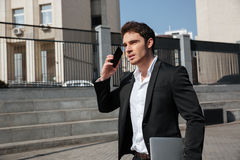 Serious young businessman walking outdoors talking by phone. Royalty Free Stock Photography