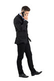 Serious young businessman walking and talking on his cellphone side view Stock Photography