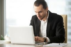 Serious young businessman working on laptop at work in office. Stock Photography