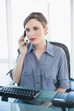 Serious young businesswoman phoning with her smartphone sitting at her desk Stock Images