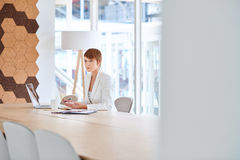Serious young businesswoman thinking at her desk in modern offic. Young busineswoman looking away with a serious and thoughtful expression while sitting at a Stock Photo