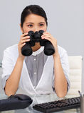 Serious young Businesswoman using binoculars Royalty Free Stock Photo