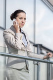 Serious young businesswoman using smart phone at office railing Stock Image