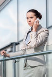 Serious young businesswoman using smart phone at office railing Royalty Free Stock Image