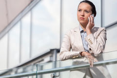Serious young businesswoman using smart phone at office railing Stock Photo