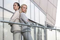Serious young businesswomen standing back to back at office railing Stock Photo