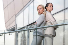 Serious young businesswomen standing back to back at office railing Royalty Free Stock Photo