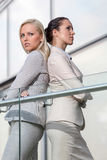 Serious young businesswomen standing back to back at office railing Royalty Free Stock Images