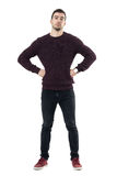 Serious young casual man with hands on waist looking at camera. Full body length portrait isolated over white studio background Royalty Free Stock Photo
