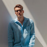 Serious young casual man leaning on a grey wall Royalty Free Stock Photography