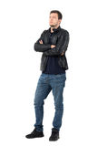 Serious young casual man in leather jacket and jeans with crossed arms looking away. Full body length portrait isolated over white studio background Royalty Free Stock Image