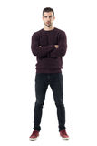 Serious young casual man in maroon sweater with crossed arms looking at camera. Stock Photos
