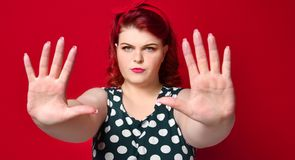 Serious young caucasian woman showing stop gesture with her hand. royalty free stock photo