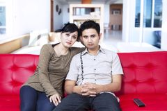 Serious young couple watching television Stock Photo