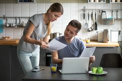Serious young couple worried discussing utility bills in the kit. Serious millennial couple worried about high utility bills or rent payment reading papers in stock photo