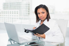 Serious young dark haired businesswoman filling her schedule Stock Photo