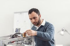 Serious young engineer getting 3D printer ready for work Royalty Free Stock Images