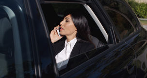 Serious young executive on phone in limousine Royalty Free Stock Photos