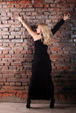 Serious young fashion woman. Young serious fashion woman in black dress over brick wall royalty free stock image