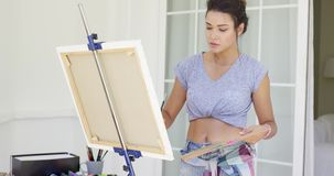 Serious young female artist painting outdoors stock footage