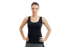 A serious young fitness girl stands up straight and keeps her hands on the sides. Of isolated on white background Royalty Free Stock Images