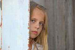 Serious young girl. Young girl with a somber expression peeking around old door Royalty Free Stock Images