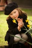 Serious young girl in beret stroking daffodil Royalty Free Stock Photo