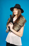 A serious young  girl in a black hat with a gun in his hand Royalty Free Stock Photos