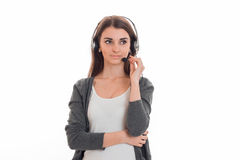 Serious young girl in gray jacket and headphones worth straight and looks toward Royalty Free Stock Photo