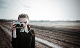 Serious young girl photographing by the old film camera. Outdoor portrait in field stock photo