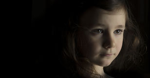 Serious young girl. Portrait of young girl with serious expression on black with copy space Royalty Free Stock Image