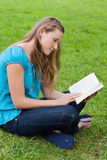 Serious young girl reading a book Royalty Free Stock Photos