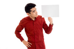 Serious young guy in red t-shirt with empty placard in his hands isolated on white background Stock Photography