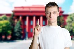 Serious young guy showing thumbs up against background of univer. Sity. The man calls for attention, caution. The concept of an important statement, information Royalty Free Stock Photos