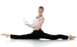 Serious young gymnast posing with laptop Royalty Free Stock Images