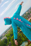 Serious young handsome man in crocodile costume near castle wall Royalty Free Stock Photo