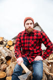 Serious young handsome man sitting on logs and holding axe Stock Photography