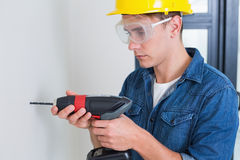 Serious young handyman using a drill Royalty Free Stock Images