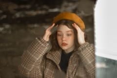 Serious young hipster female in beige hat looking down stock photos