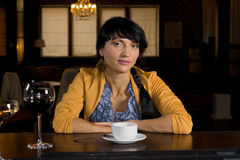 Serious young Hispanic woman drinking coffee. Seated at a bar counter looking directly at the camera with a thoughtful expression royalty free stock image