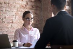 Serious young HR manager woman interviewing male candidate royalty free stock images