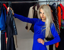Serious young lady choosing a dress in clothing store Royalty Free Stock Photos