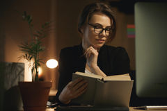 Serious young lady designer sitting indoors at night reading book. Photo of serious young lady designer sitting indoors at night using computer and reading book royalty free stock photos