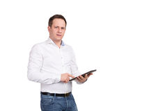 Serious young male executive using digital tablet against white background, looking at camera Royalty Free Stock Photos