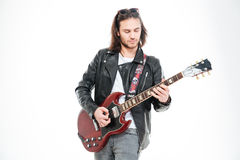 Serious young male guitarist standing and playing electric guitar Stock Photo