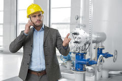 Serious young male manager using cell phone in industry Stock Images