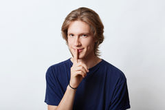 Serious young male with trendy hairstyle, wearing casual t-shirt, showing silence sign, keeping his finger on mouth, asking to kee Stock Photos