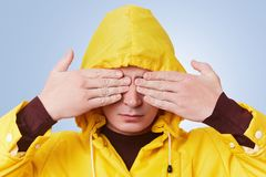 Serious young male wears yellow anorak and hood, covers eyes with hands, anticipates for surprise or tries to hide himself. Fashio. Nable hipster guy gestures Royalty Free Stock Photos